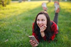 Portret u?miechni?ty kobiety lying on the beach na zielonej trawie i u?ywa? outdoors smartphone zdjęcie stock