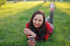 Portret u?miechni?ty kobiety lying on the beach na zielonej trawie i u?ywa? outdoors smartphone zdjęcie royalty free