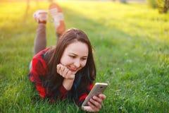Portret u?miechni?ty kobiety lying on the beach na zielonej trawie i u?ywa? outdoors smartphone obraz stock