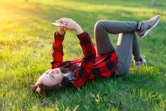 Portret u?miechni?ty kobiety lying on the beach na zielonej trawie i u?ywa? outdoors smartphone zdjęcia royalty free