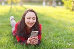 Portret u?miechni?ty kobiety lying on the beach na zielonej trawie i u?ywa? outdoors smartphone zdjęcia stock