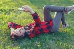 Portret u?miechni?ty kobiety lying on the beach na zielonej trawie i u?ywa? outdoors smartphone fotografia stock
