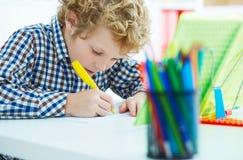 Portret uczeń w szkolnej klasie bierze notatki podczas writing lekci Edukaci, dzieciństwa, pracy domowej i szkoły pojęcie, Zdjęcia Royalty Free