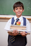 Portret ucznia mienia książki i jabłko Obrazy Royalty Free