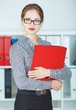 Portret ufna biznesowa kobieta patrzeje kamerę z dokument skrzynką w rękach Obrazy Stock