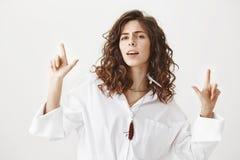 Portret ufna chłodno caucasian kobieta wskazuje up lub pokazuje armatnich gesty z zwycięzcy wyrażeniem, marszczy brwi i Zdjęcie Stock