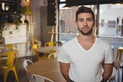 Portret ufna kelner pozycja w kawiarni zdjęcia stock