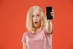 Portret ufna przypadkowa dziewczyna pokazuje pustego ekranu telefon komórkowego odizolowywającego nad czerwonym tłem Obrazy Stock
