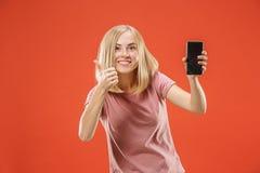Portret ufna przypadkowa dziewczyna pokazuje pustego ekranu telefon komórkowego odizolowywającego nad czerwonym tłem Fotografia Royalty Free