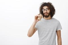 Portret ufny atrakcyjny szczupły męski barista w modnej koszulce i eyewear, pije kawę od filiżanki i ono wpatruje się zdjęcie stock