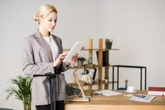 portret ufny bizneswoman używa pastylkę przy miejsce pracy podczas gdy stojący fotografia royalty free
