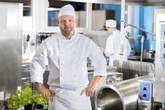 Portret ufny i uśmiechnięty szef kuchni robi jedzeniu w wielkiej kuchni Fotografia Stock