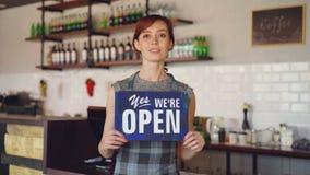 Portret ufny kobieta małego biznesu właściciela mienia ` jesteśmy otwartym ` znaka pozycją w jej sklep z kawą i ono uśmiecha się zbiory