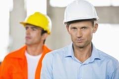 Portret ufny męski architekt przy budową z coworker w tle Zdjęcie Stock