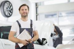 Portret ufny męski utrzymanie inżynier z schowkiem w samochodowym remontowym sklepie Obrazy Royalty Free