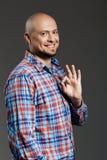 Portret ufny przystojny rozochocony w średnim wieku mężczyzna ono uśmiecha się przy kamerą pokazuje ok gest nad popielatym w szko Zdjęcie Stock