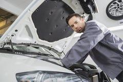 Portret ufny samiec naprawy pracownik naprawia samochodowego silnika w remontowym sklepie Fotografia Royalty Free