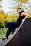 Portret ufny sprawność fizyczna facet Mężczyzna pozy na łyżwowej rampie przeciw tłu jesień lasowy spadek Zdjęcia Stock