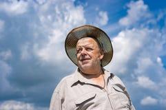 Portret Ukraiński starszy rolnik w słomianym kapeluszu przeciw błękitnemu chmurnemu niebu obraz royalty free
