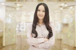 Portret uśmiechać się długiej z włosami młodej kobiety z rękami krzyżować w kamerę i patrzeć, indoors Obrazy Stock