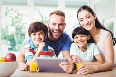 Portret uśmiechnięta rodzina używa cyfrową pastylkę Zdjęcia Royalty Free