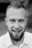 Portret uśmiechnięty młody czerwony włosiany mężczyzna z brodą czarny i biały Obraz Stock
