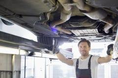 Portret uśmiechnięty remontowy pracownik egzamininuje samochód w warsztacie Zdjęcia Stock