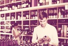 Portret uradowany męski klient bierze butelkę wino w sklepie Obraz Royalty Free