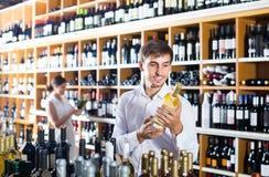 Portret uradowany męski klient bierze butelkę wino w sklepie Zdjęcia Stock