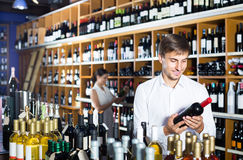 Portret uradowany męski klient bierze butelkę wino w sklepie Zdjęcia Royalty Free