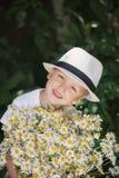 Portret urocza chłopiec w kapeluszu z dużym białym bukietem rumianki zdjęcie stock