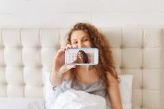 Portret urocza kobieta robi selfie na mądrze telefonie podczas gdy kłamstwo Obrazy Royalty Free