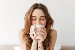 Portret urocza kobieta z pięknym brown włosianym pije morn zdjęcia stock