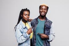Portret urocza młoda afro amerykańska para wskazuje palce przy each inny odizolowywającym nad białym tłem obraz stock