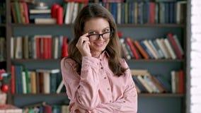 Portret urocza młoda bibliotekarska kobiety pozycja w bibliotecznym atrakcyjnym studenckim uśmiechniętym zakończeniu w górę zbiory