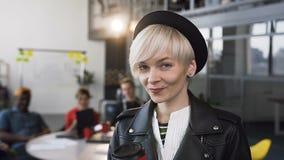 Portret urocza młoda modniś kobiety pozycja w biurze podczas gdy pijący kawę lub blondynki dziewczyny ono uśmiecha się herbaciane zbiory