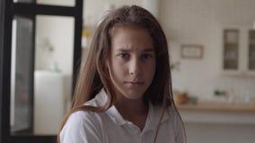 Portret urocza mała dziewczyna patrzeje kamerę ono uśmiecha się szczęśliwie i pokazuje emocje na jej twarzy w domu Beztroski zbiory
