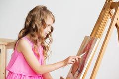 Portret urocza mała dziewczynka maluje obrazek w studiu fotografia stock