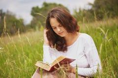 Portret urocza piękna kobieta z atrakcyjnym spojrzeniem czyta książkę w na wolnym powietrzu, siedzi w zieleni polu, cieszy się la fotografia stock