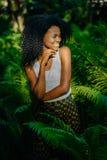 Portret uroczy ładny afrykanina model z zielonymi eyeshadows i pomadką patrzeje na boku i uroczy ono uśmiecha się podczas gdy Zdjęcie Royalty Free