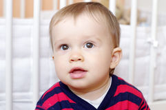 Portret uroczy chłopiec wiek 1 rok przeciw białemu łóżku Zdjęcie Royalty Free
