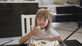 Portret uroczy małe dziecko je świeżego cukierki tort w domu Powabna dziewczyna z długie włosy w białej sukni zbiory wideo