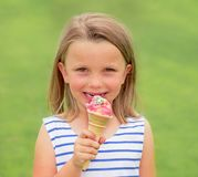 Portret uroczy, piękny blond młodej dziewczyny lat je wyśmienicie lody uśmiecha się szczęśliwy odosobnionego na zieleni gr i Zdjęcie Royalty Free