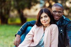 Portret Uroczy wielokulturowy pary obsiadanie na trawie w patrzeć i parku obraz royalty free