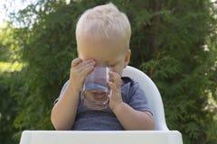 Portret van één jaar het oude drinkwater van het blonde Kaukasische kind in kristalglas in openlucht Stock Foto's