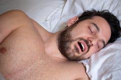 Portret van één mensenslaap in bed en het snurken stock foto