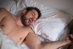 Portret van één mensenslaap in bed en het snurken stock afbeelding