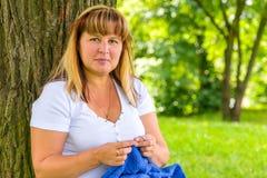 Portret van 50 éénjarigenvrouw belast met het breien Stock Afbeelding