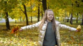 Portret van aanbiddelijk meisje met geel bladerenboeket in daling stock videobeelden