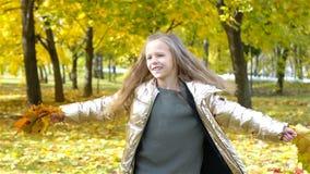 Portret van aanbiddelijk meisje met geel bladerenboeket in daling stock footage